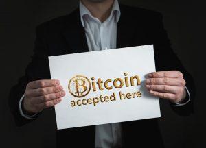 Muškarac u odjelu koji drži Bitcoin natpis