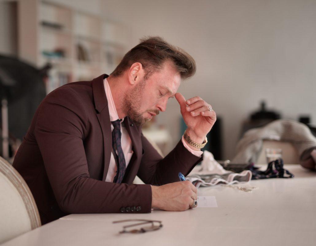 Muškarac u sakou gleda u sto sa rukom na čelu